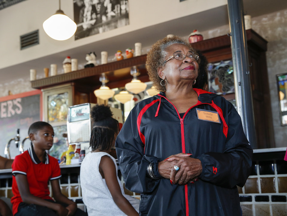Photo - Marilyn Luper Hildreth stands inside Kaiser's Grateful Bean as children reenact the first Katz Drug Store sit-in, one of the first civil rights protests in the nation, in Oklahoma City, Saturday, Aug. 18, 2018. Hildreth participated in the first Katz Drug Store sit-in on August 19, 1958, which was led by her mother, Clara Luper. Photo by Nate Billings, The Oklahoman