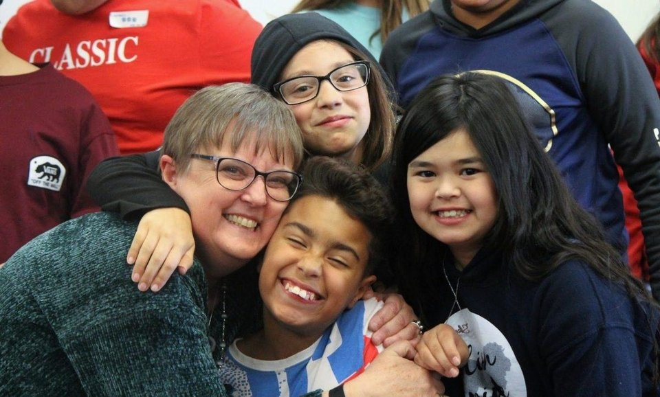 Photo -  Anne Ham poses in January with her fifth-grade students at Lincoln Elementary School in Norman. Ham decided to retire one year early because of health concerns stemming from COVID-19. [Anne Ham/provided]