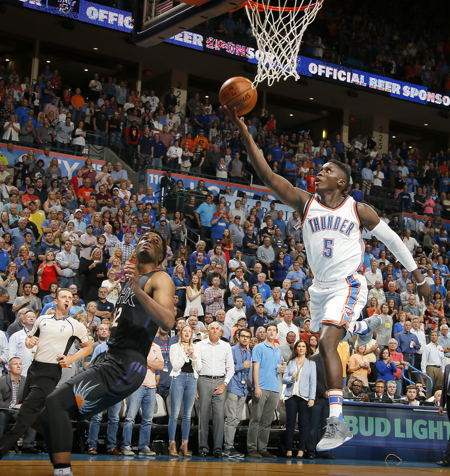 Photo - Oklahoma City's Victor Oladipo (5) goes to the basket as Phoenix's T.J. Warren (12) watches during an NBA basketball game between the Oklahoma City Thunder and the Phoenix Suns at Chesapeake Energy Arena in Oklahoma City, Friday, Oct. 28, 2016. Photo by Bryan Terry, The Oklahoman