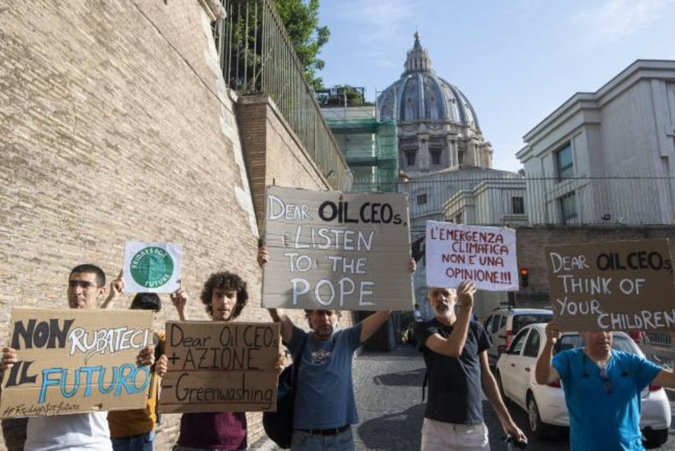 Photo -  Activists hold up signs outside the Vatican on Friday as Pope Francis meets with oil executives. [AP PHOTO]