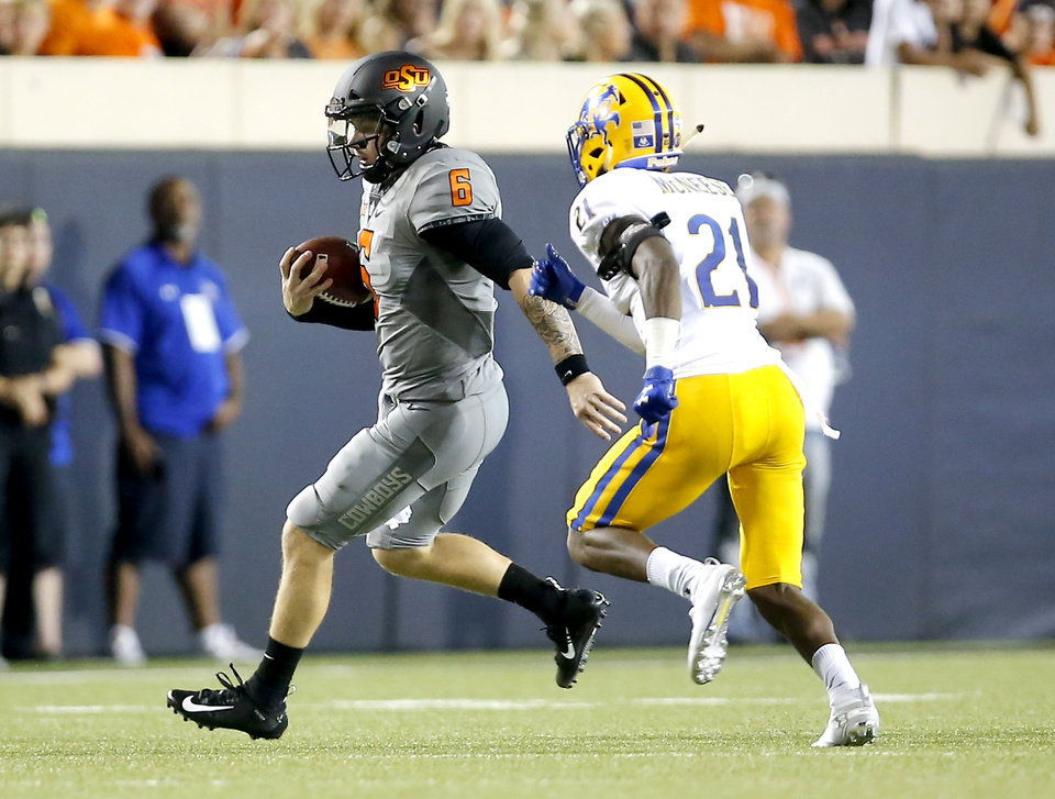 Photo - Oklahoma State's Dru Brown (6) rushes as McNeese State's Andre Sam (21) chases him in the third quarter during the college football game between the Oklahoma State Cowboys and the McNeese State Cowboys at Boone Pickens Stadium in Stillwater, Okla., Saturday, Sept. 7, 2019. [Sarah Phipps/The Oklahoman]