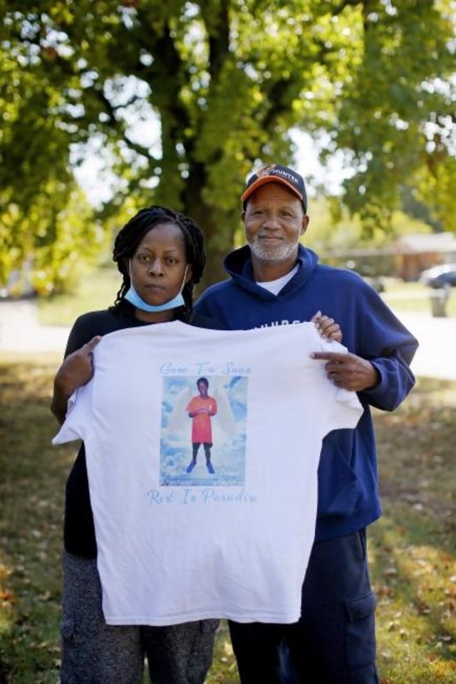 Photo -  Roy and Vanesser Jones hold a shirt with a picture of their son Roland Jones outside their Midwest City home, Thursday, Oct. 22, 2020. Roland Jones, 12, was shot and killed Sept. 30 in Midwest City. [Bryan Terry/The Oklahoman]