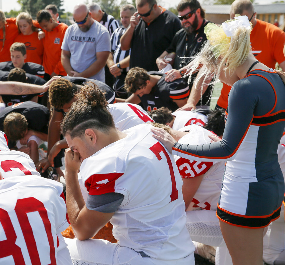 Photo - Cushing cheerleader Katelyn Jones places her hand on the back of McLoud's Roberto Valadez (7) as both teams pray on the field before a high school football game between McLoud and Cushing at O'Dell Field in Cushing, Okla., Saturday, Oct. 6, 2018. The game was postponed and moved from McLoud after Kaylen Thomas, a McLoud High School student, was fatally shot the previous day. Photo by Nate Billings, The Oklahoman