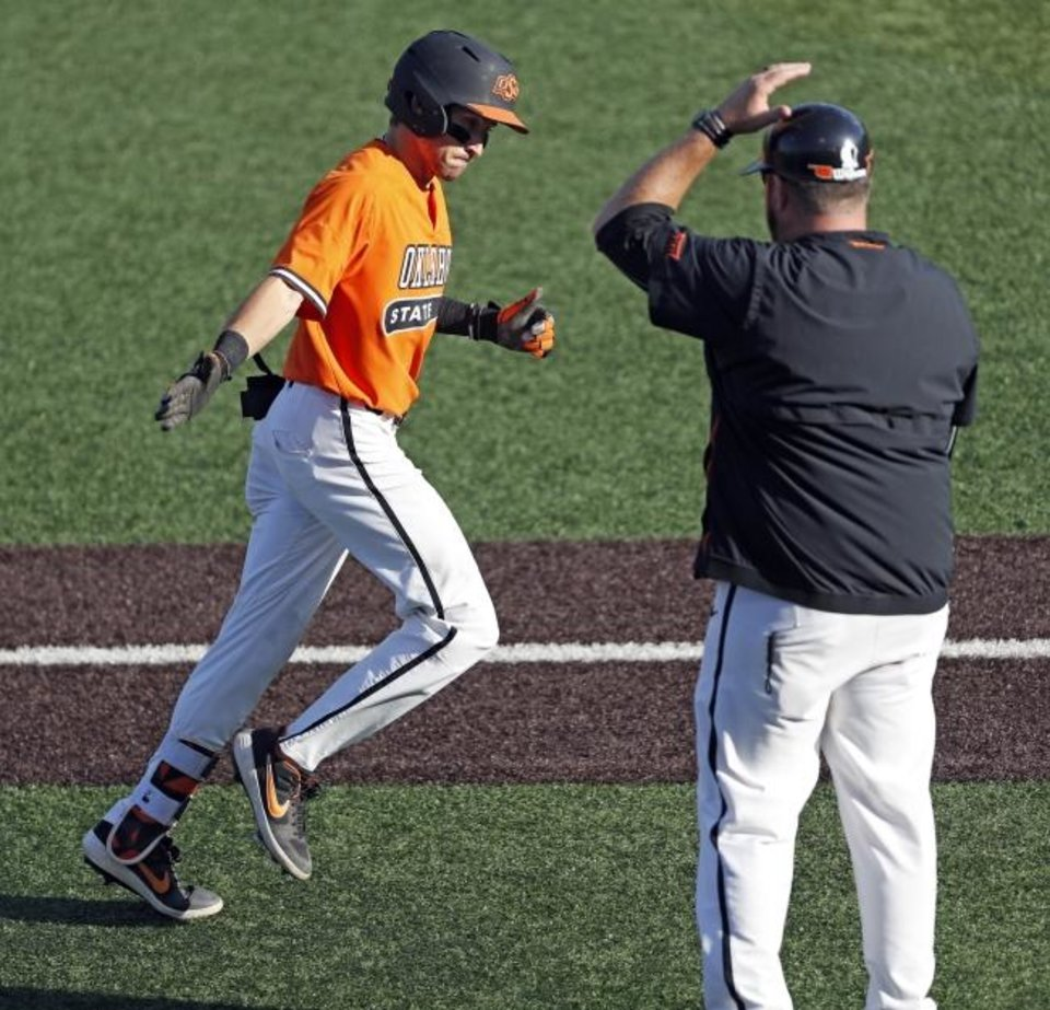 Photo -  Oklahoma State's Hueston Morrill (1) reaches out to assistant coach James Vilade after hitting a home run in the fifth inning against Texas Tech on Saturday. [AP Photo/Brad Tollefson]