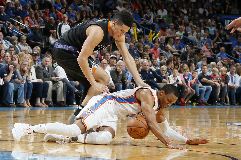 Photo - Oklahoma City's Russell Westbrook (0) dives for the ball under Phoenix's Devin Booker (1) during an NBA basketball game between the Oklahoma City Thunder and the Phoenix Suns at Chesapeake Energy Arena in Oklahoma City, Friday, Oct. 28, 2016. Photo by Bryan Terry, The Oklahoman