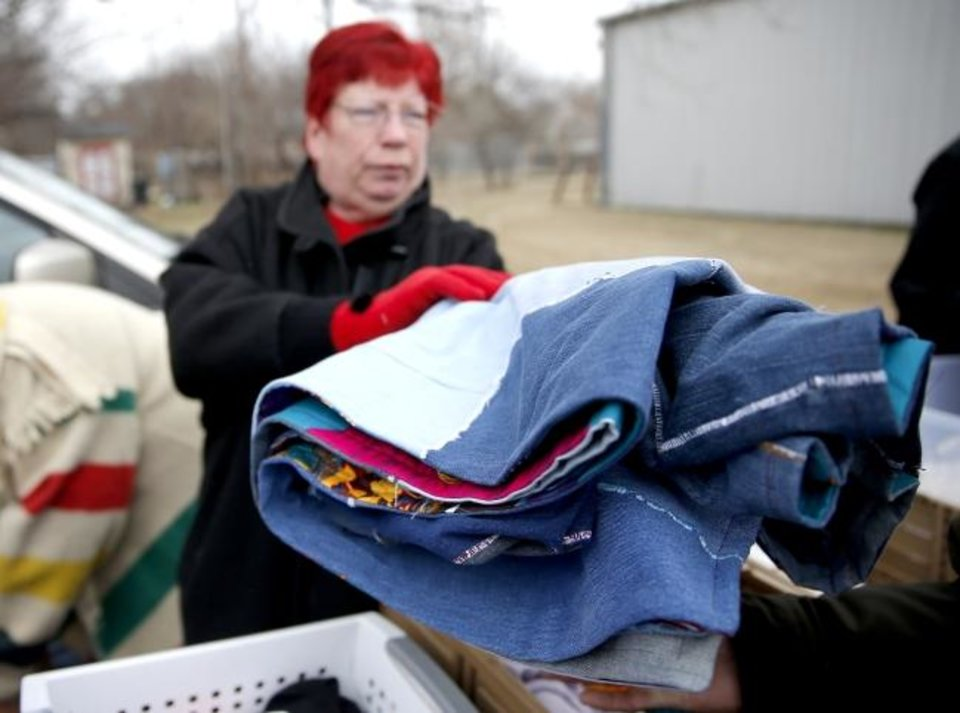 Photo -  Sandra Roark hands out a quilt she made of used jeans during the Ice Angels ministry outreach in south Oklahoma City. [Sarah Phipps/The Oklahoman]