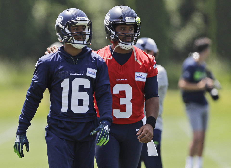 Photo - Seattle Seahawks quarterback Russell Wilson (3) walks off the field with wide receiver Tyler Lockett (16) following an organized team activity Tuesday, June 4, 2019, at the team's NFL football training facility in Renton, Wash. (AP Photo/Ted S. Warren)