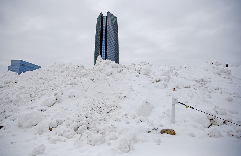 Photo - A large snow pile of snow removed from downtown Oklahoma City streets is pictured by the Chesapeake Energy Arena, Tuesday, Feb. 16, 2021. [Sarah Phipps/The Oklahoman]