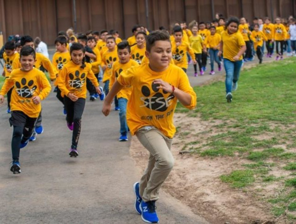 Photo -  Students in the Santa Fe South Elementary School running club try out their new running shoes. The Oklahoma City Memorial Kids Marathon recently teamed up with Oklahoma Cleats for Kids to provide new running shoes to the school's running club members. [PHOTO PROVIDED]