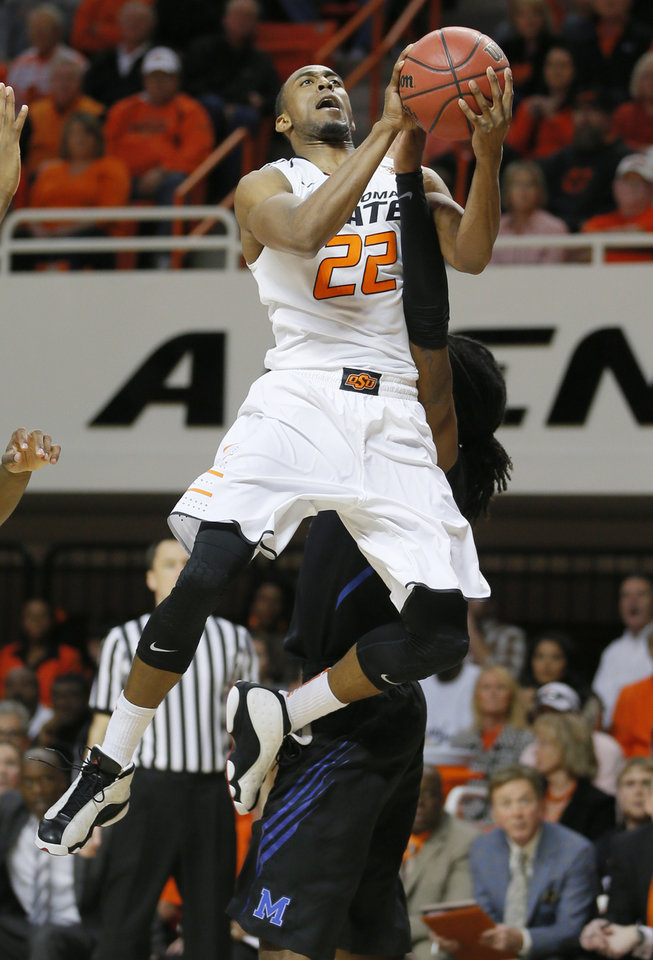 Photo - Oklahoma State's Markel Brown (22) goes to the basket past Memphis' Shaq Goodwin (2) during an NCAA college basketball game between Oklahoma State and Memphis at Gallagher-Iba Arena in Stillwater, Okla., Tuesday, Nov. 19, 2013. Photo by Bryan Terry, The Oklahoman