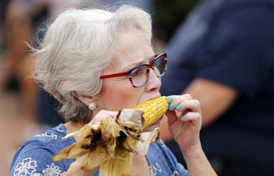 Photo -  Donna VanDusen, of Oklahoma City, enjoys roasted corn at the Oklahoma State Fair on Thursday.