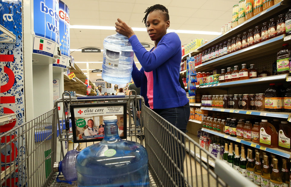 Photo - Marie Michel loads a filled water bottled into her shopping cart Thursday inside a Kroger store in Houston in preparation for Hurricane Harvey. The National Hurricane Center is forecasting Harvey will become a major hurricane to hit the middle Texas coastline. (Godofredo A. Vasquez/Houston Chronicle via Associated Press)