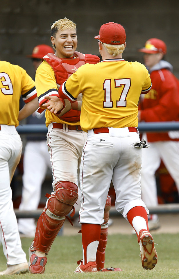 Photo - Dale catcher Jono Johnson, facing camera, celebrates the Pirates' win with teammate Tanner Collins after the final out of the Class 2A baseball state semifinal game at Shawnee High School on Friday, May 10, 2019.  Dale defeated Oktaha, 6-0.   [Jim Beckel/The Oklahoman]