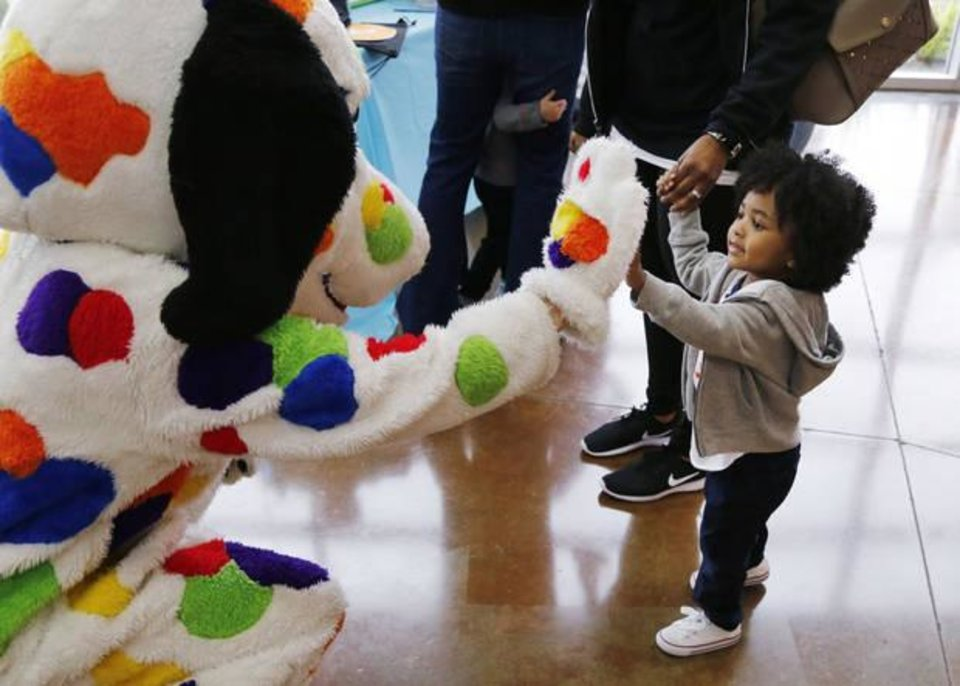Photo -  E.J. Rembert, 2, gives a high-five to a dog mascot. [PHOTO BY PAUL HELLSTERN, THE OKLAHOMAN]