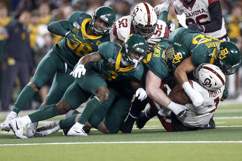 Photo - Baylor safety Chris Miller (3), defensive tackle James Lynch (93) and linebacker Terrel Bernard (26) tackle Oklahoma quarterback Jalen Hurts (1) during an NCAA college football game, in Waco, Texas, Saturday, Nov. 16, 2019. (Ian Maule/Tulsa World via AP)