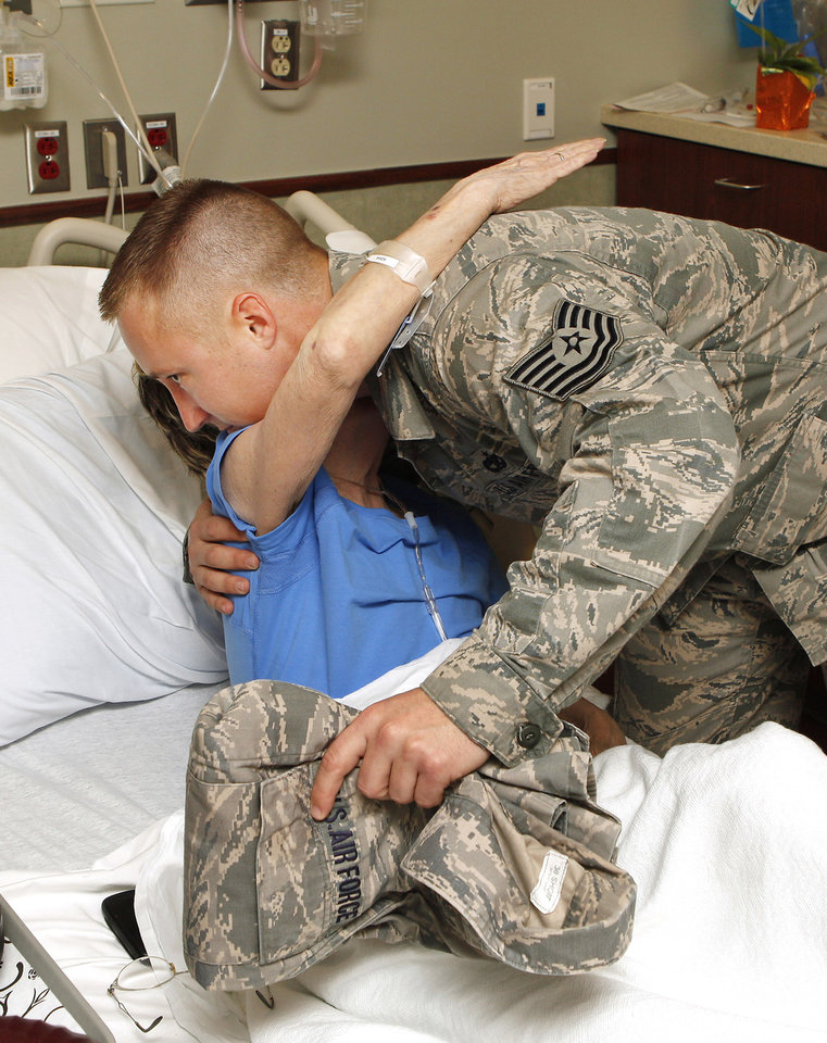 Photo - Tornado victim Sandra Adams hugs Air Force Tech. Sgt. Drew Stanley, 137th Air Refueling Wing, after returning his air force jacket to him in her hospital room at Integris Southwest Medical Center in Oklahoma City Thursday, May 23, 2013. Stanley came upon Adams during rescue efforts after her home was destroyed by Monday's tornado and wrapped her in his Air Force jacket before she was taken to the hospital. Photo by Paul B. Southerland, The Oklahoman