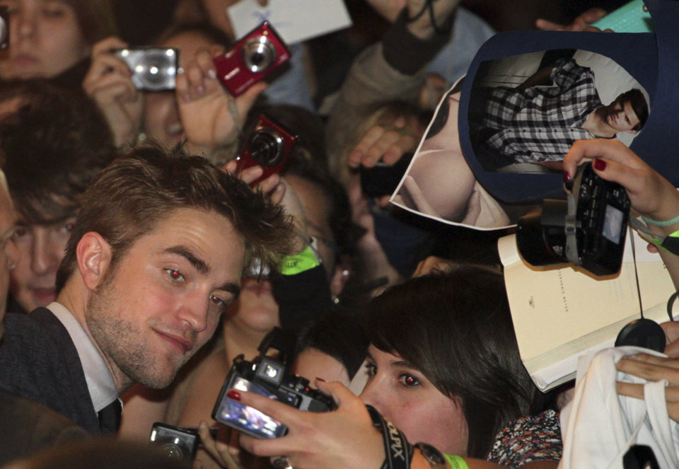 Photo - British actor Robert Pattinson takes pictures with a fans before a film premiere of 'Twilight Breaking Dawn Part 1' in Barcelona, Spain, Thursday, Nov. 17, 2011. (AP Photo/Job Vermeulen) ORG XMIT: MF118