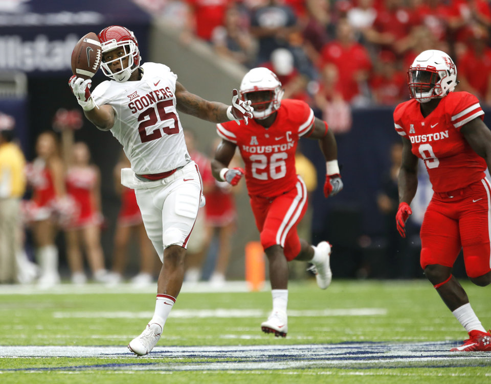 Photo - Oklahoma's Joe Mixon (25) catches the ball in front of Houston's Brandon Wilson (26) and Matthew Adams (9) during the AdvoCare Texas Kickoff college football game between the University of Oklahoma Sooners (OU) and the Houston Cougars at NRG Stadium in Houston, Saturday, Sept. 3, 2016. Photo by Bryan Terry, The Oklahoman