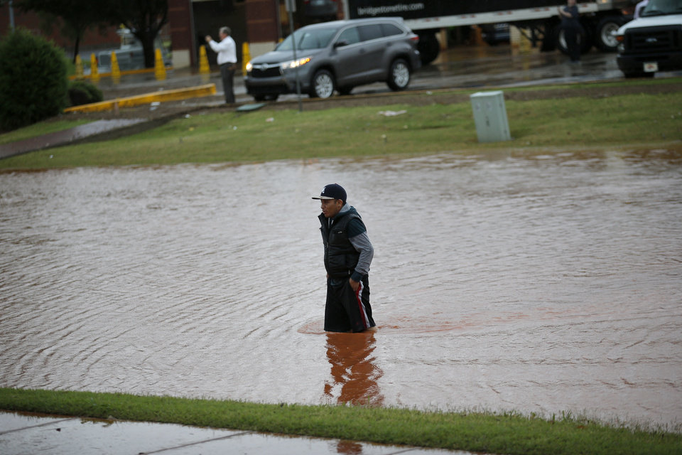 Photo -  A man walks from his stranded car in flood waters Thursday near Pennsylvania Avenue and Memorial Road after heavy rain moved through the area. [Photo by Sarah Phipps, The Oklahoman]