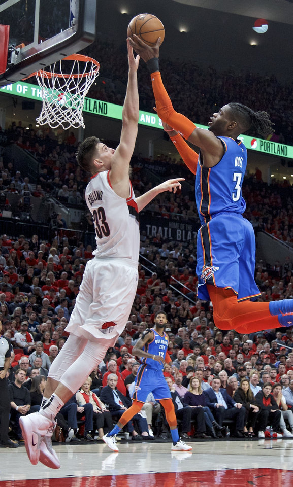 Photo - Oklahoma City Thunder forward Nerlens Noel, right, has a shot blocked by Portland Trail Blazers forward Zach Collins during the first half of Game 2 of an NBA basketball first-round playoff series Tuesday, April 16, 2019, in Portland, Ore. (AP Photo/Craig Mitchelldyer)