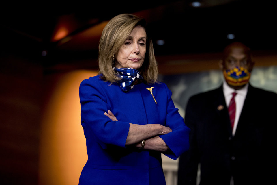Photo -  House Speaker Nancy Pelosi of Calif., left, accompanied by Rep. Dwight Evans, D-Pa., right, listens to a question from a reporter during a news conference on Capitol Hill in Washington, Friday, July 24, 2020, on the extension of federal unemployment benefits. (AP Photo/Andrew Harnik)