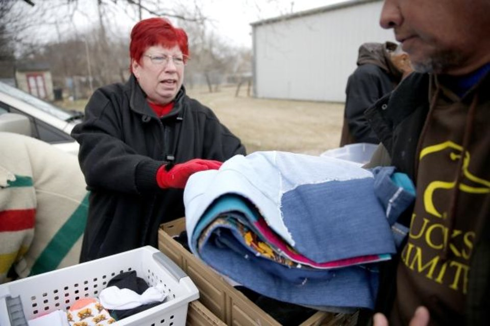 Photo - Sandra Roark hands out a quilt made of used jeans in Oklahoma City, Wednesday, Jan. 29, 2020. The Ice Angels Ministry handed the quilts out to those in need. [Sarah Phipps/The Oklahoman]