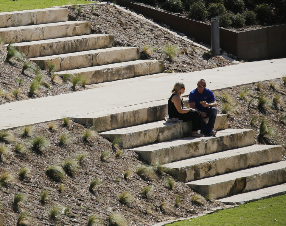 Photo -  A couple sit on steps near the lake Monday at the Myriad Botanical Gardens. [Photo by Doug Hoke, The Oklahoman]