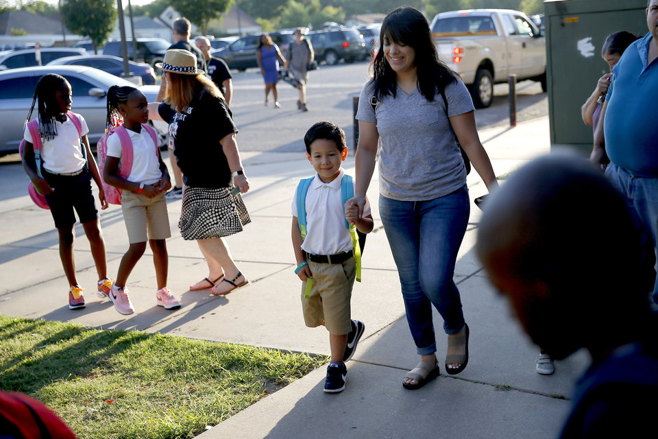 Photo - Crystal Sanchez walks with her son Jeremiah Sanchez, 5, as he begins kindergarten on the first day of school at Britton Elementary in Oklahoma City, Monday, Aug. 12, 2019. [Bryan Terry/The Oklahoman]