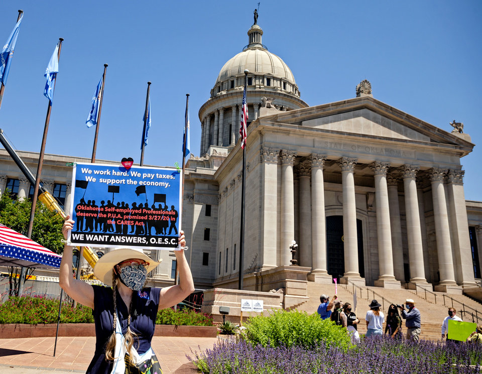 Photo - Jennifer Robertson, carries a sign as she gathers with other self-employed Oklahomans at the Oklahoma state Capitol to protest the lack of unemployment payments on Monday, May 18, 2020, in Oklahoma City, Okla..  [Chris Landsberger/The Oklahoman]