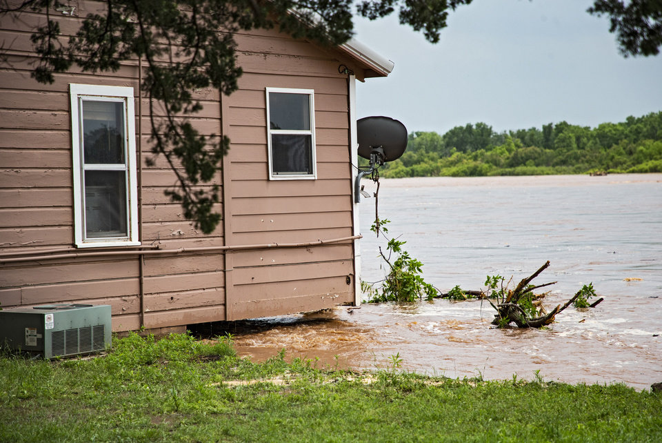 Photo - Flood waters rushing down the Cimarron  River wash away the ground under a home in the Twin Lakes community near Cimarron City, Okla. on Wednesday, May 22, 2019.  [Chris Landsberger/The Oklahoman]