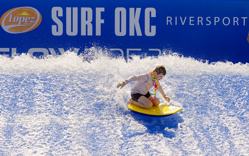 Photo - Surfers show off their skills during the opening ceremony for the new SURF OKC at the Riversport Adventures in Oklahoma City, Okla. on Friday, Aug. 28, 2020. The first surfing experience in Oklahoma will open Saturday in the Boathouse District. The Flowrider surfer was built with funds from MAPS 3, a one-cent sales tax initiative to fund projects that enhance the quality of life for metro area residents.  [Chris Landsberger/The Oklahoman]
