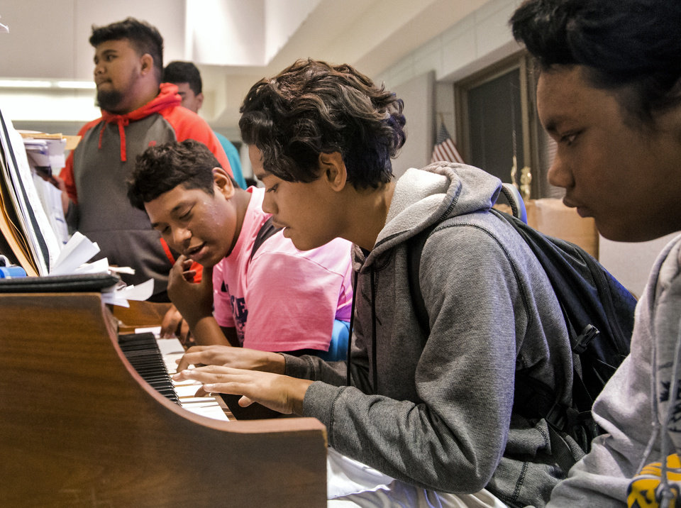 Photo -  Students from the Marshall Islands gather around the piano as they take part in a multicultural choir practice at Enid High School.   [Photo by Chris Landsberger, The Oklahoman]