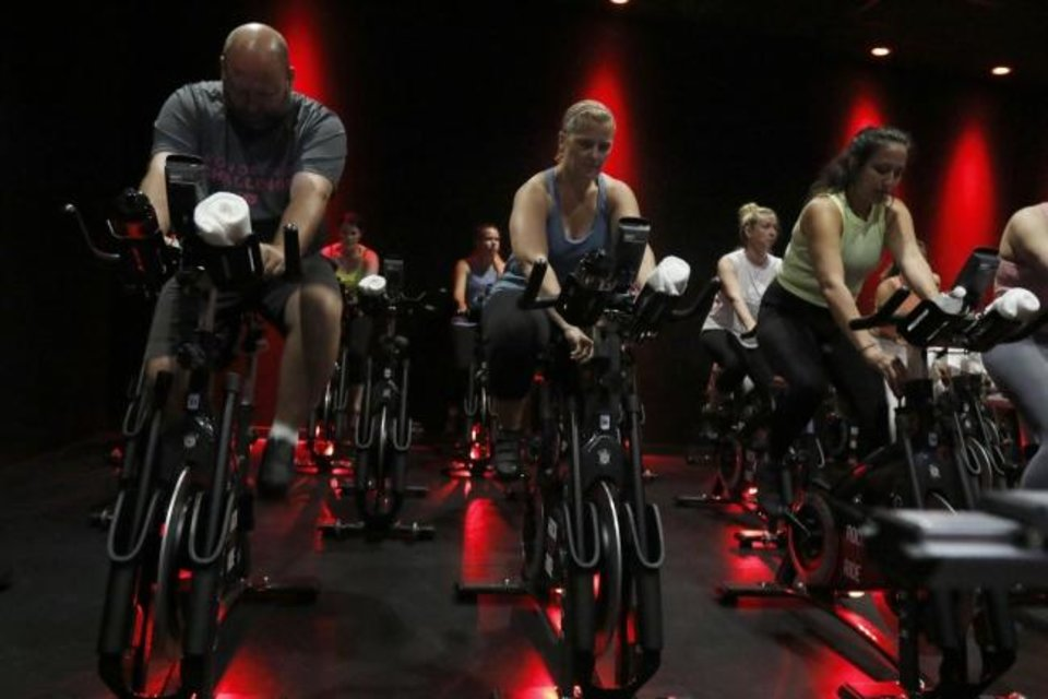 Photo -  Class members participate in the 9:30 a.m. class at the new CycleBar studio in Norman on Thursday. [PAXSON HAWS/THE OKLAHOMAN]