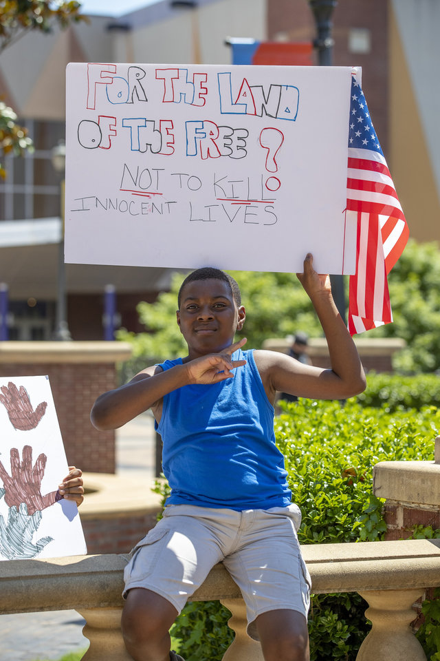 Photo - A protester holds a sign during a Black Lives Matter OKC Rally in the Bricktown area of Oklahoma City on Saturday, June 6, 2020. Photo by Alonzo Adams for The Oklahoman.