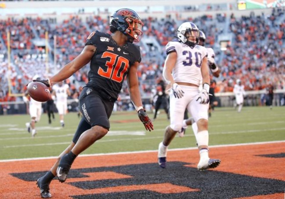 Photo -  Oklahoma State's Chuba Hubbard reacts in front of TCU's Garret Wallow after scoring a 67-yard touchdown earlier this season. [Sarah Phipps/The Oklahoman]