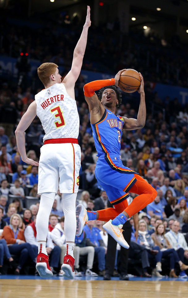 Photo - Oklahoma City's Shai Gilgeous-Alexander (2) shoots as Atlanta's Kevin Huerter (3) defends during the NBA basketball game between the Oklahoma City Thunder and the Atlanta Hawks at the Chesapeake Energy Arena in Oklahoma City,Friday, Jan. 24, 2020.  [Sarah Phipps/The Oklahoman]