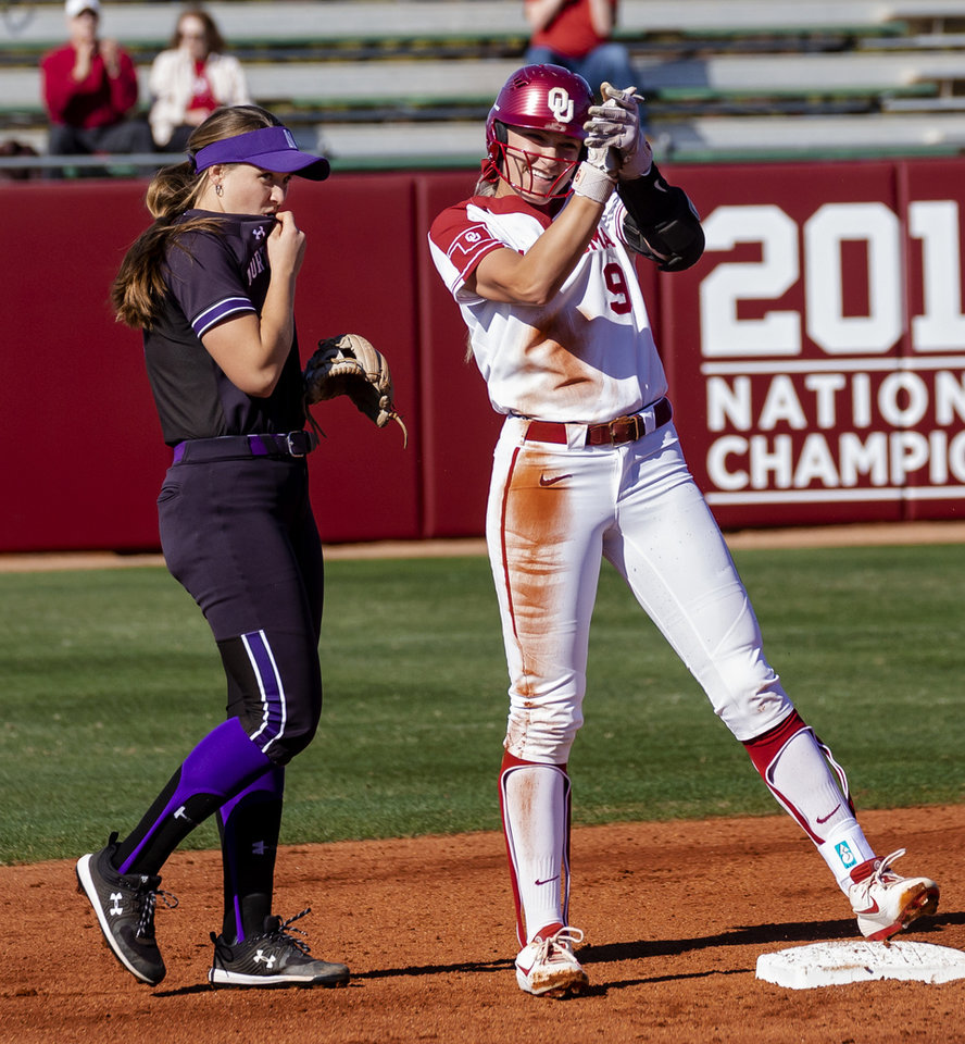 Photo - Oklahoma's Kinzie Hansen (9) reacts in front of Northwestern's Maeve Nelson (4) after driving runs in to score during the college softball game between the University of Oklahoma Sooners (OU) and Northwester University Wildcats (NU) at Marita Hynes Field in Norman, Okla. on Friday, Feb. 28, 2020.    [Chris Landsberger/The Oklahoman]