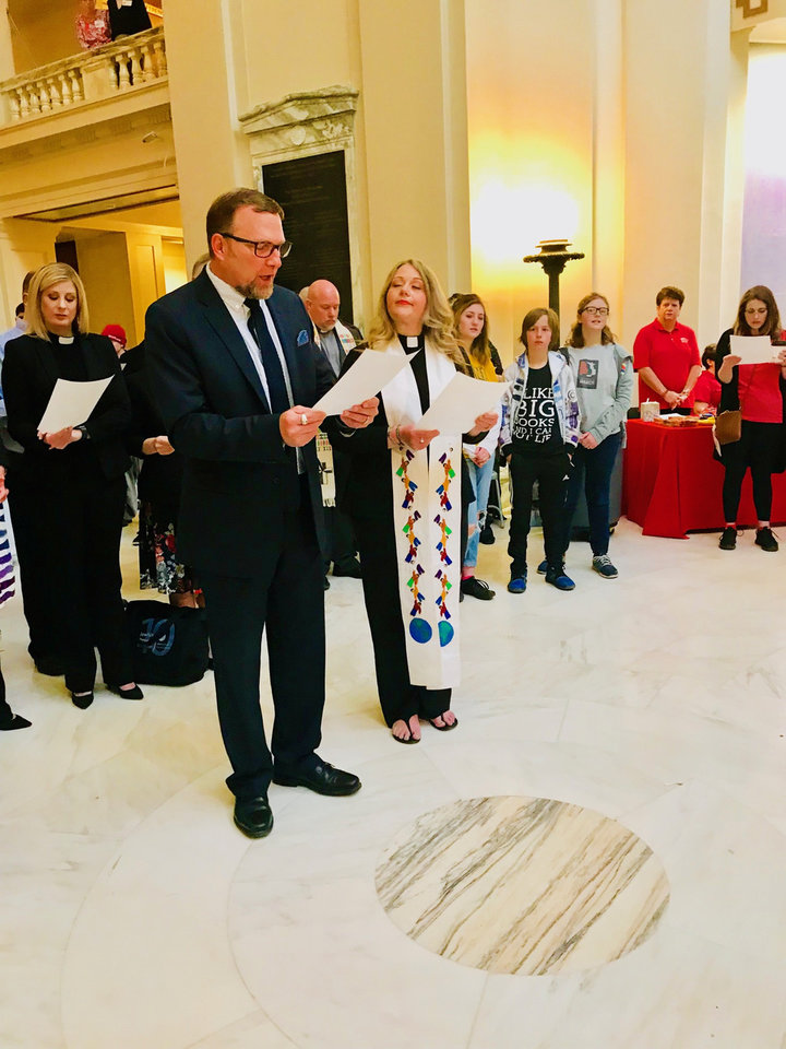 Photo - The Rev. Todd Littleton and the Rev. Tiffany Monroe lead the crowd in a community litany at a prayer gathering on Thursday at the State Capitol. [Photo by Carla Hinton, The Oklahoman]