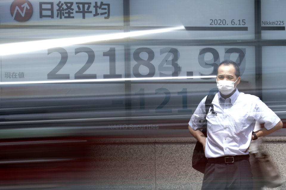 Photo -  A man stands in front of an electronic stock board showing Japan's Nikkei 225 index as a car passes by at a securities firm in Tokyo Monday, June 15, 2020. Asian shares were mostly lower Monday on concern over a resurgence of coronavirus cases and pessimism after Wall Street posted its worst week in nearly three months. (AP Photo/Eugene Hoshiko)