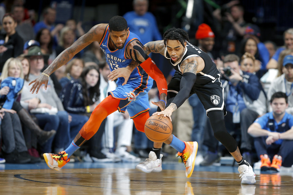 Photo - Oklahoma City's Paul George (13) defends Brooklyn's D'Angelo Russell (1) during an NBA basketball game between the Oklahoma City Thunder and the Brooklyn Nets at Chesapeake Energy Arena in Oklahoma City, Wednesday, March 13, 2019. Oklahoma City won 108-96. Photo by Bryan Terry, The Oklahoman