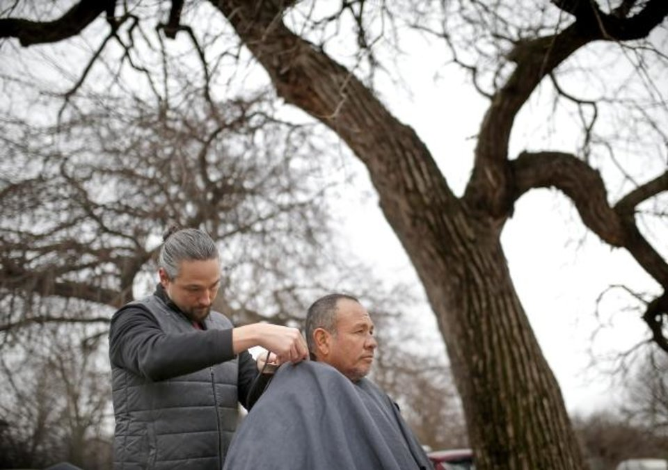 Photo -  Volunteer barber Craig Jackson cuts Victor Garcia's hair during the Ice Angels ministry weekly outreach in south Oklahoma City. [Sarah Phipps/The Oklahoman]
