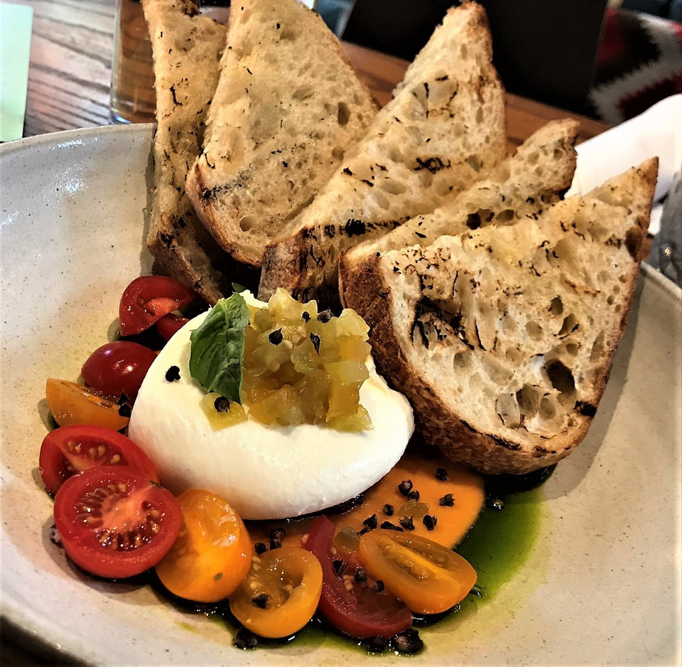 Photo -  Burrata cheese is served with three kinds of tomato, and sourdough bread at The Jones Assembly in downtown Oklahoma City. [Dave Cathey/The Oklahoman]