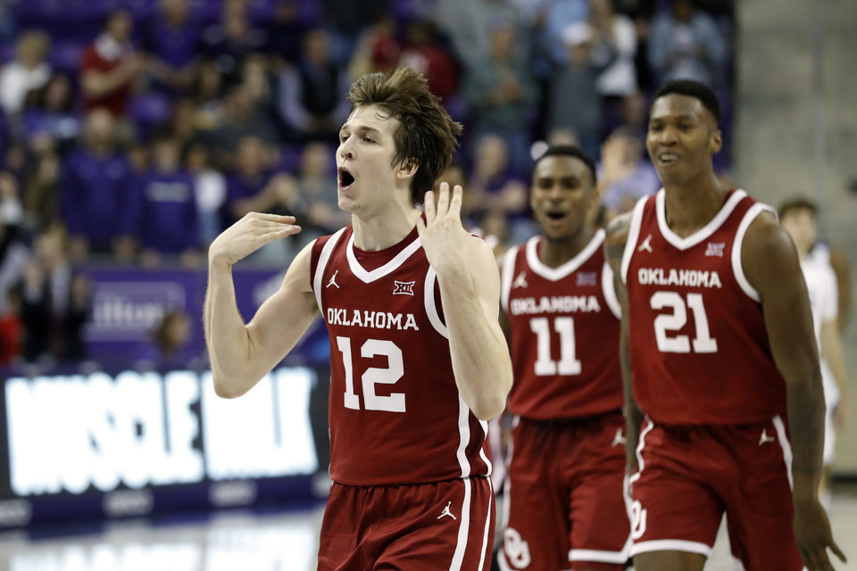 Photo - Oklahoma guard Austin Reaves (12), guard De'Vion Harmon (11) and forward Kristian Doolittle (21) celebrate in the final seconds of the second half of an NCAA college basketball game against TCU in Fort Worth, Texas, Saturday, March 7, 2020. Oklahoma won 78-76. (AP Photo/Tony Gutierrez)