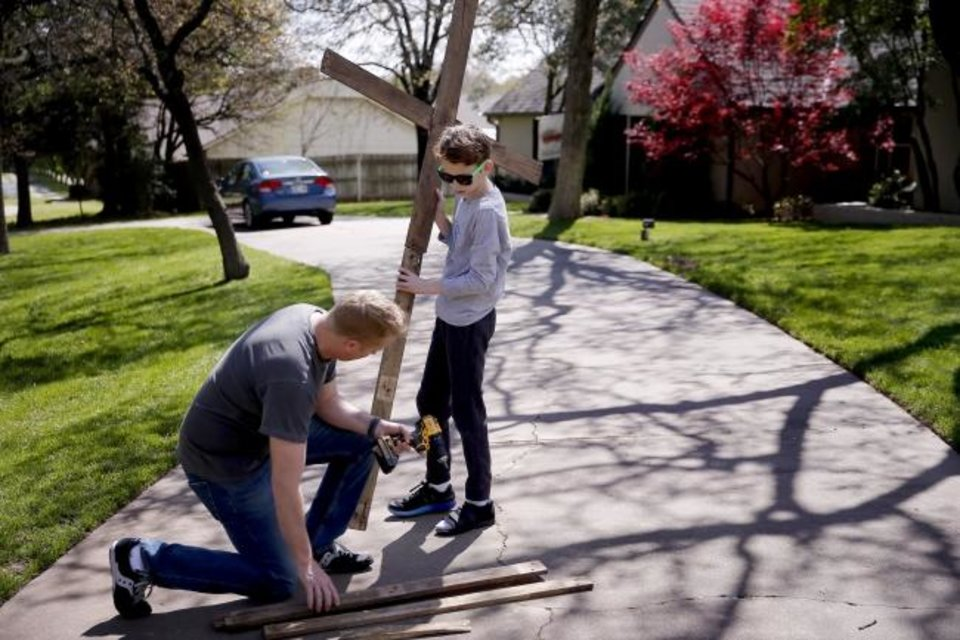Photo -  Ross Cash and his son Brecken, 11, assemble a scene for a drive-thru Stations of the Cross outside their Edmond home. [Bryan Terry/The Oklahoman]