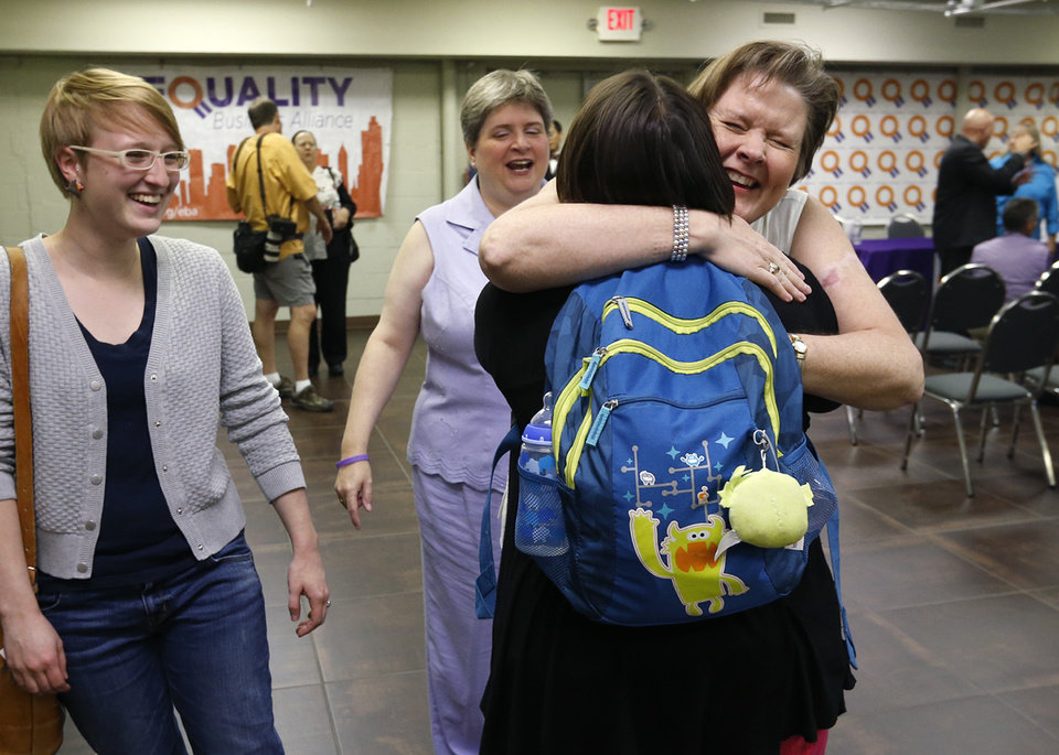 Photo - Mary Bishop (right) hugs a supporter as her partner Sharon Baldwin (center) and supporter Jennie Wachowski (left) stand near after a press conference at the Dennis R. Neill Equality Center in Tulsa, Okla. on Monday, October 6, 2014. Bishop and Baldwin were the first same-sex couple in Oklahoma to receive a marriage license. MATT BARNARD/Tulsa World