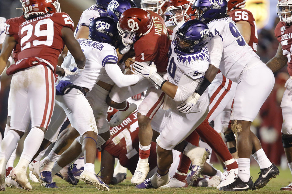 Photo - Oklahoma's Jalen Hurts (1) is pulled down after getting a first down on a late fourth-down attempt during an NCAA football game between the University of Oklahoma Sooners (OU) and the TCU Horned Frogs at Gaylord Family-Oklahoma Memorial Stadium in Norman, Okla., Saturday, Nov. 23, 2019. Oklahoma won 28-24. [Bryan Terry/The Oklahoman]