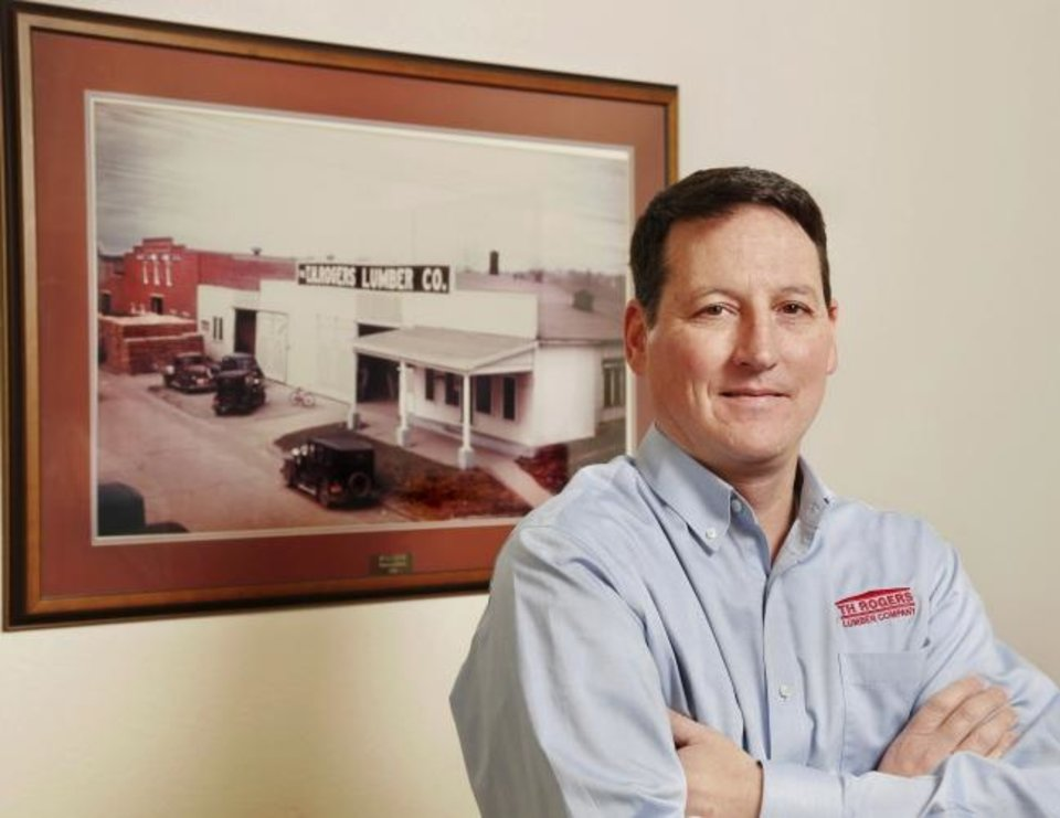 Photo -  Jonathan Kennedy, president of T.H. Rogers Lumber Co., stands in front of a photograph of an early store in McAlester. [JIM BECKEL/THE OKLAHOMAN]