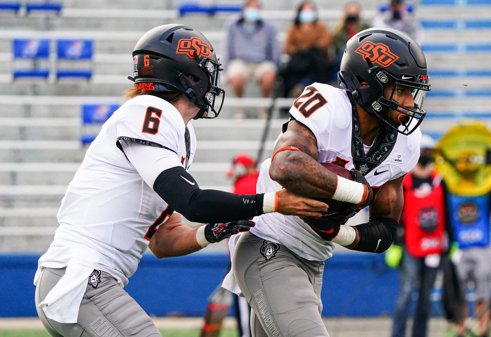 Photo - Oct 3, 2020; Lawrence, Kansas, USA; Oklahoma State Cowboys running back Dominic Richardson (20) takes the handoff from quarterback Ethan Bullock (6) during the second half against the Kansas Jayhawks at David Booth Kansas Memorial Stadium. Mandatory Credit: Jay Biggerstaff-USA TODAY Sports