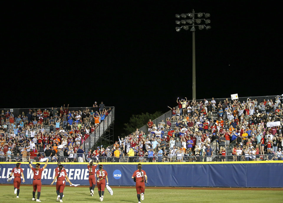 Photo - OU pumps up fans after the right field light went out during a Women's College World Series between Oklahoma State (OSU) and Oklahoma at USA Softball Hall of Fame Stadium in Oklahoma City,  Friday, May 31, 2019.  [Sarah Phipps/The Oklahoman]