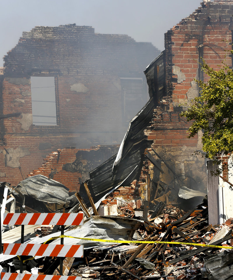 Photo -  A weekend fire in in downtown Seminole destroyed multiple historic brick buildings on Main Street. Monday, smoke continued to rise from the twisted and charred rubble. [Photo by Jim Beckel, The Oklahoman]
